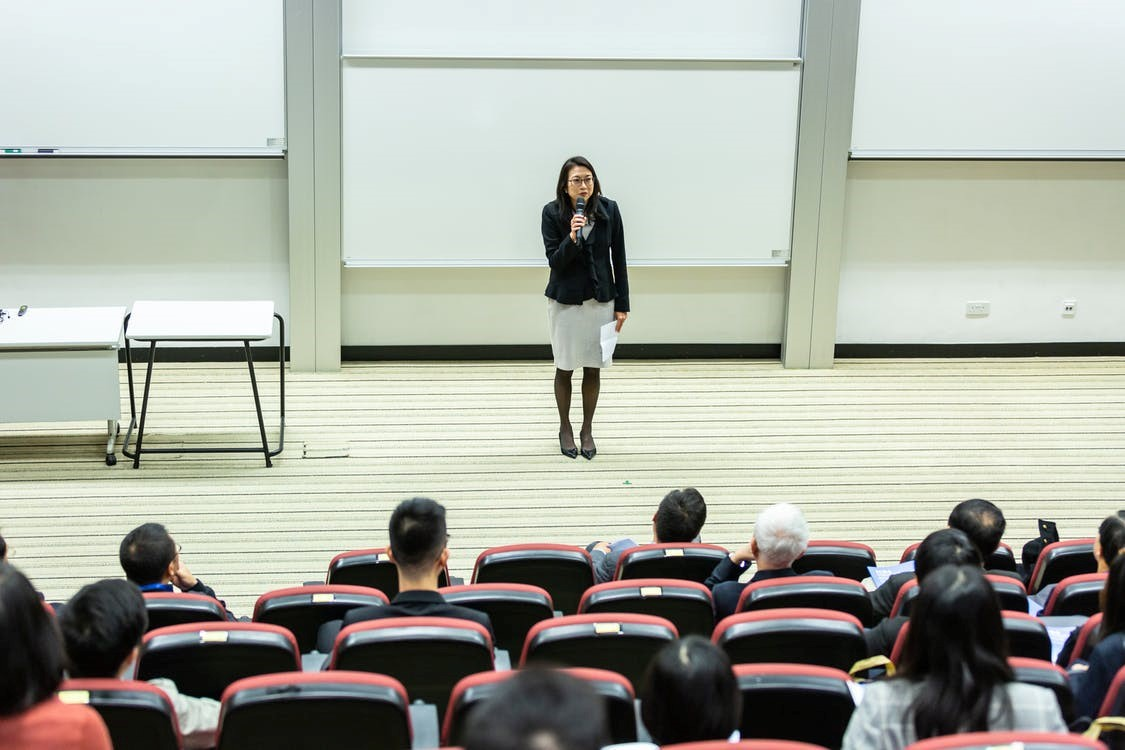 A person giving a presentation to a class in stadium seating. Pexels.com credit: ICSA
